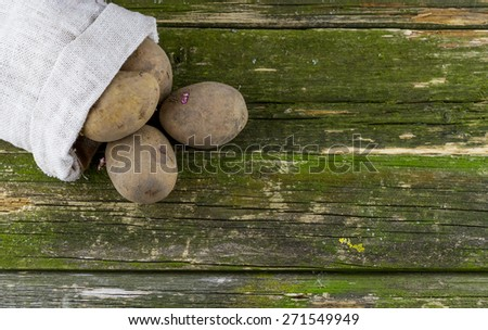 Heap of potatoes in the bag on old grunge wooden background with place for your text - stock photo