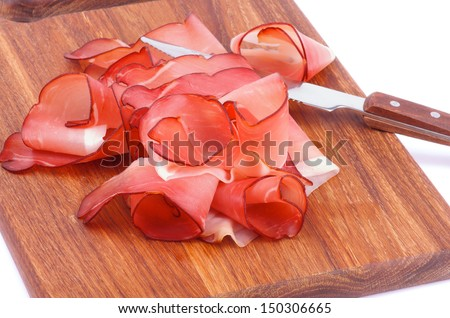 Heap of Prosciutto Slices and Kitchen Knife on Wooden Cutting Board closeup on white background - stock photo