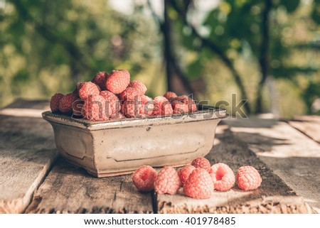 Heap of raspberries and bowl with raspberries on wood boards - stock photo