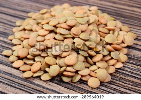 Heap of raw green lentil lying on wooden background, concept for healthy nutrition and eating - stock photo