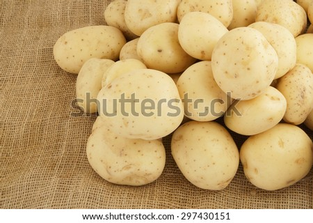 Heap of raw young potatoes on burlap background - stock photo