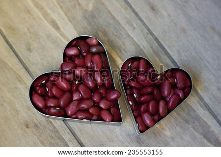 Heap of red beans are in heart shape on wooden background - stock photo