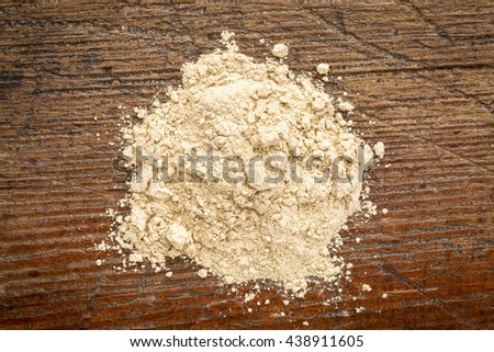heap of red maca root powder against rustic weathered wood - stock photo