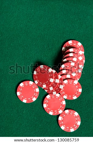 Heap of red poker chips on the green table. Symbol of risky entertainment - stock photo