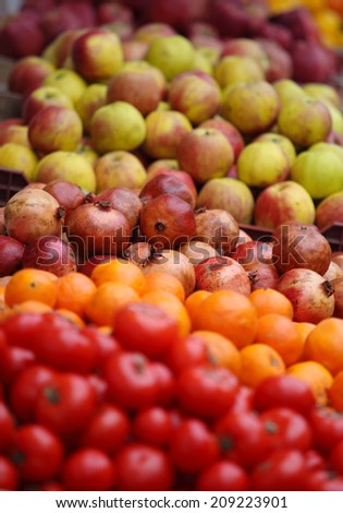 Heap of ripe fruits and vegetables. Apples, pomegranates and tomatoes - stock photo