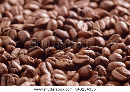 Heap of roasted coffee beans photographed from low angle. Scattered coffee beans background. Closeup with shallow depth of field and fine details. - stock photo