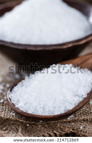 Heap of Salt (close-up shot) on dark wooden table - stock photo