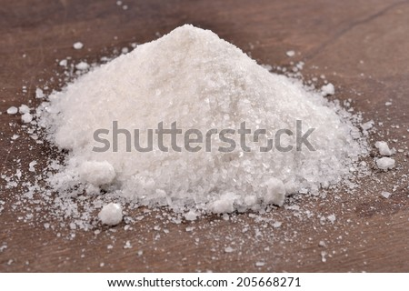 Heap of salt on a wooden background - stock photo