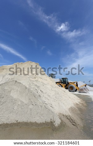 Heap of sand and gravel with bulldozer against blue sky - stock photo