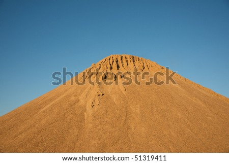 Heap of sand or dune in the desert against clear blue sky
