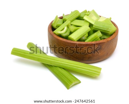 heap of sliced celery in wood bowl, isolated on white background  - stock photo