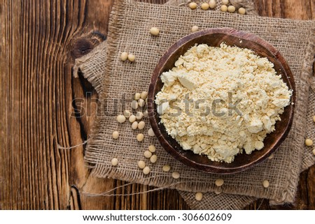 Heap of Soy Flour (close-up shot) on rustic wooden table - stock photo