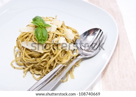 Heap of spaghetti on a plate with fresh homemade pesto, basil, Parmesan and cutlery