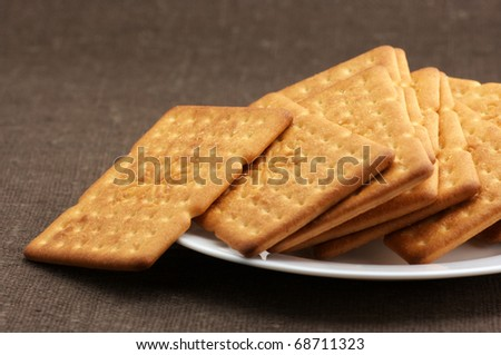 Heap of square crackers in white plate on brown canvas. - stock photo