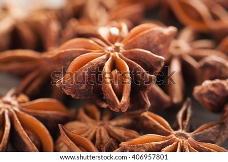 Heap of star anise on a wooden table, closeup macro shot, selective focus - stock photo