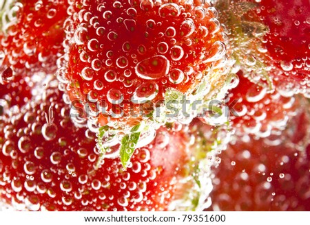 heap of strawberries in water with bubbles - stock photo