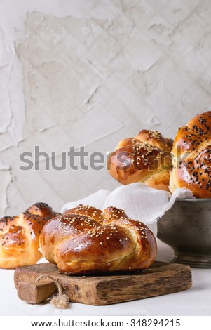 Heap of sweet round sabbath challah bread with white and black sesame seeds in vintage metal bowl and on small cutting board over white table with plastered wall at background. - stock photo