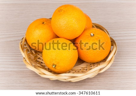 Heap of tangerine in wicker basket on wooden table - stock photo