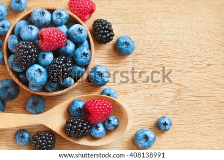 Heap of tasty berries on wooden table. Close up, top view, high resolution product. Harvest Concept - stock photo