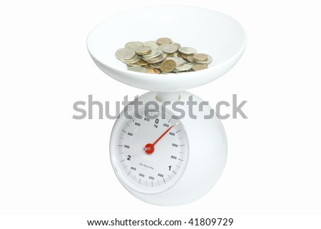 heap of the coins on a kitchen scales under the white background - stock photo