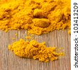 Heap of turmeric on isolated wood background - stock photo