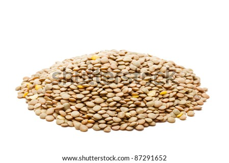 Heap of uncooked lentils over white background