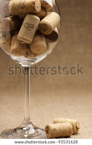 Heap of used vintage wine corks in wineglass on burlap. - stock photo