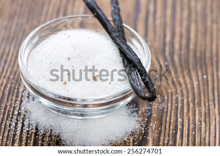 Heap of Vanilla Sugar (white) on wooden background - stock photo