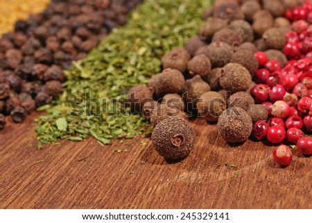 Heap of various kinds of dry spices on a wooden background - stock photo