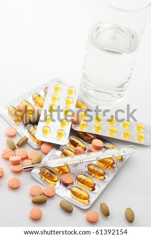 Heap of various pills, thermometer and glass of water on light background. - stock photo