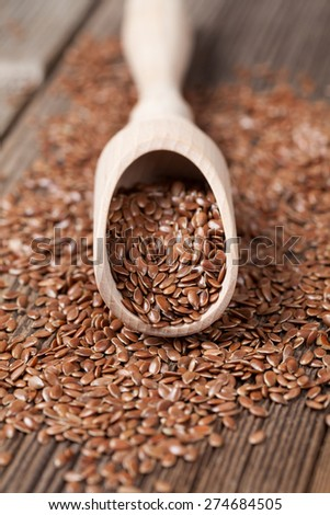 Heap of vegetarian nutrition flax seeds with omega fat in spoon on vintage wooden background - stock photo