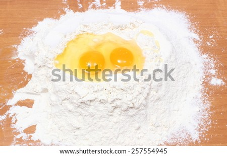 Heap of wheat flour and broken egg, baking ingredients, preparing yeast cake - stock photo