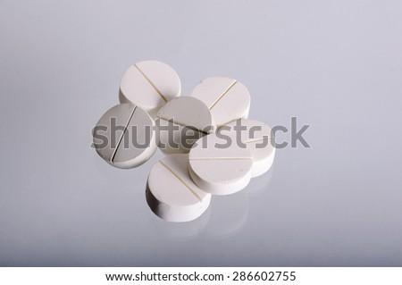 Heap of white pills closeup. On a white background - stock photo