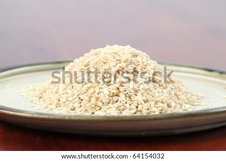 Heap of white sesame seeds on a plate - stock photo