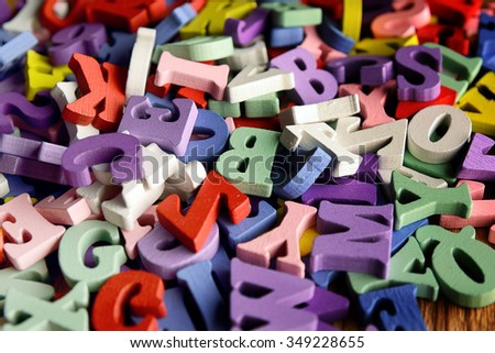 Heap of wooden  colored alphabet letters close up