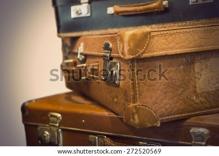 Heap of worn vintage leather suitcases in sepia tone - stock photo