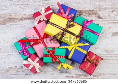 Heap of wrapped colorful gifts for Christmas, birthday or other celebration on old wooden white plank