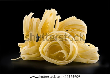 heap raw dry nest pasta with reflection isolated on black - stock photo