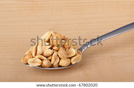 heaping spoonful peanuts on wood background stock photo edit now