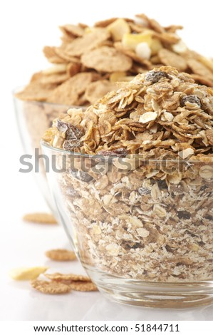 Heaps of breakfast cereals in glass bowls on white background. - stock photo