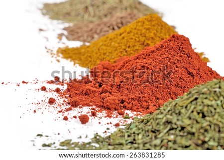 Heaps of different dry spices on a white background