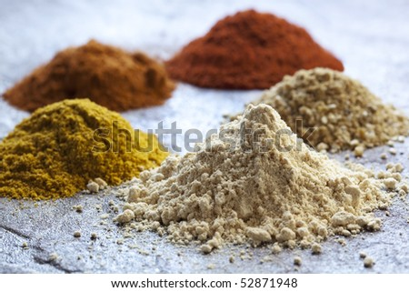 Heaps of different spices; with focus on ginger in front.