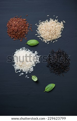 Heaps of red, brown, white and black rice kernels, above view - stock photo