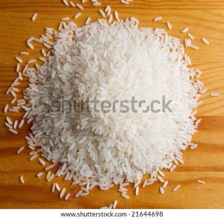 heaps of rice on wooden table - stock photo