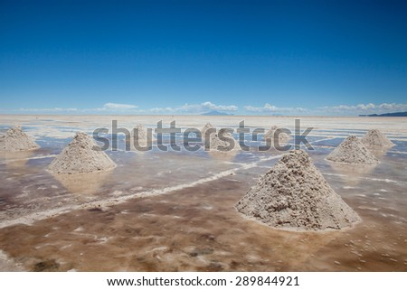 Heaps of salt in the Salares de Uyuni, Bolivia. Blue sky background with clouds - stock photo