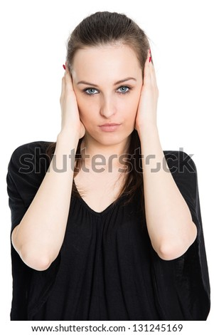 Hear no evil - attractive young brunette covering her ears with hands, isolated on white background - stock photo