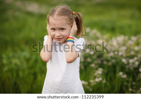 Hear no evil - Lovely little girl covering her ears with hands, doesn't want to hear anything, outdoors - stock photo