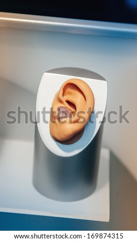 Hearing aid close-up placed inside the model of a human ear displayed at doctor's office - stock photo