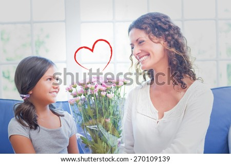 Heart against happy mother and daughter sitting on the couch with flowers - stock photo