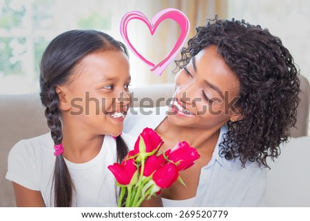 Heart against pretty mother sitting on the couch with her daughter holding roses - stock photo